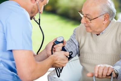 Male nurse checking blood pressure of senior men